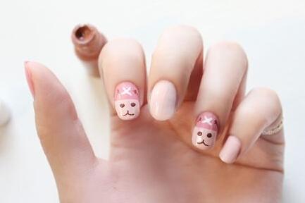 同样用巧克力色在指甲的下半部画出圆圆的眼睛和可爱的小嘴巴.