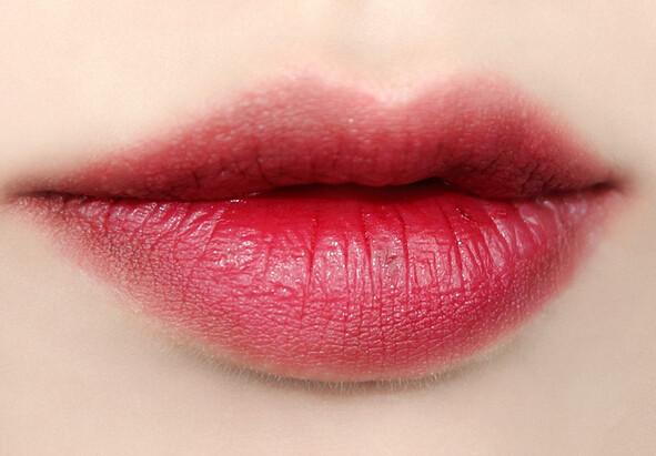 樱桃红色的唇膏涂抹唇部